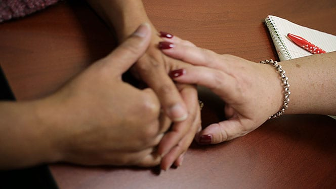 Image of one person's hand resting on another person's hand